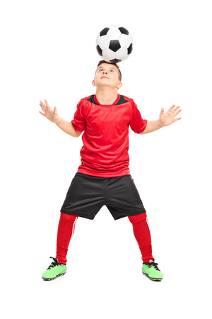 kicking ball: Full length portrait of a junior soccer player joggling with a ball isolated on white background