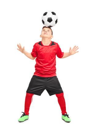 Retrato de cuerpo entero de un jugador de fútbol infantil malabares con una pelota aislados sobre fondo blanco Foto de archivo
