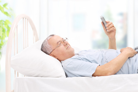 old cell phone: Senior watching something on his cell phone in bed at home