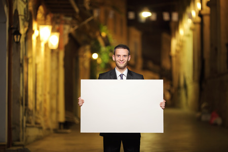 man holding sign: Businessman holding a blank panel in a city street