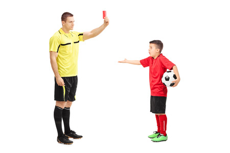 junior soccer: Football referee showing red card to a junior soccer player isolated on white background
