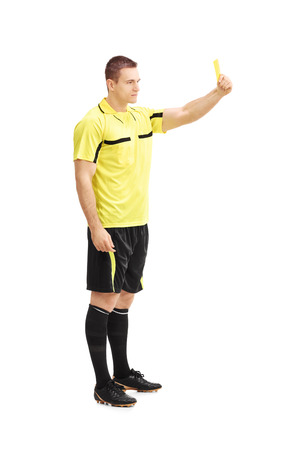arbiter: Full length portrait of a football referee showing a yellow card isolated on white background