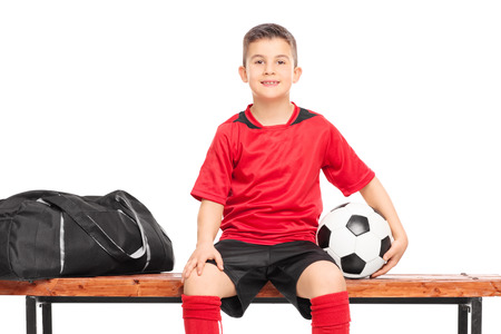 substitution: Little boy holding a soccer ball seated on a bench isolated on white background