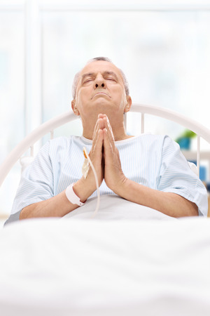 incurable: Senior patient lying in hospital bed and praying to god