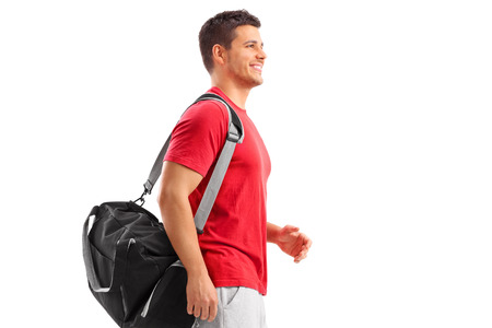 sports wear: Male athlete walking with a sport bag isolated on white background