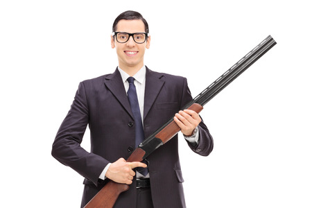 gatillo: Guardaespaldas masculina que sostiene una escopeta aislada en el fondo blanco
