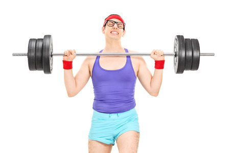 struggling: Nerdy athlete attempting to lift a weight isolated on white background Stock Photo