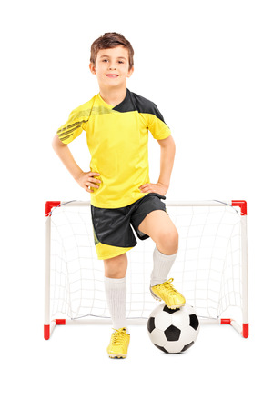 junior soccer: Full length portrait of a junior soccer player standing in front of a small goal isolated on white background