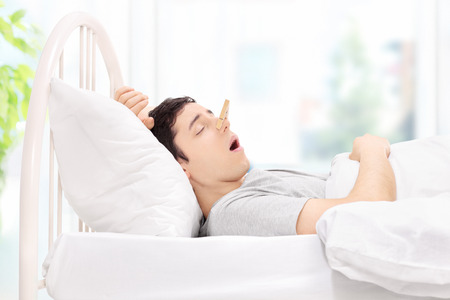 snoring: Man sleeping with a clothespin on his nose at home