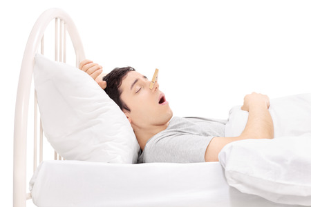 snoring: Man sleeping with a clothespin on his nose isolated on white background Stock Photo