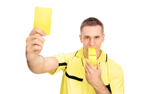 yellow card: Referee showing yellow card and blowing huge whistle isolated on white background