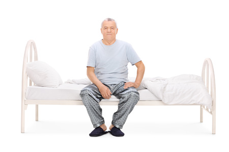 early 60s: Senior man in pajamas sitting on a bed isolated on white background