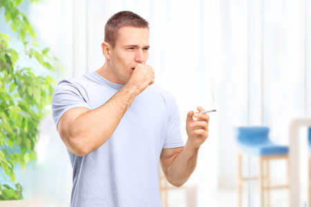 tosiendo: Hombre joven que fuma un cigarrillo y toser en casa