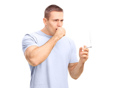 joven fumando: Hombre joven que fuma un cigarrillo y tos aislada en el fondo blanco Foto de archivo