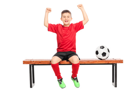 junior soccer: Joyful junior soccer player gesturing happiness seated on bench isolated on white background