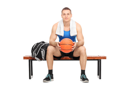 player bench: Male basketball player sitting on a bench isolated on white background Stock Photo
