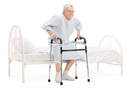 Mature patient getting up from bed with walker isolated on white background Stock Photo