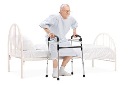 levantandose: Paciente maduro levantarse de la cama con el caminante aislado en fondo blanco Foto de archivo
