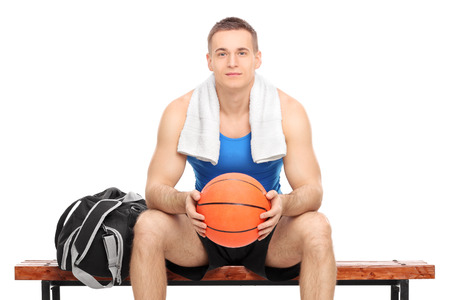 player bench: Young male basketball player sitting on a bench isolated on white background