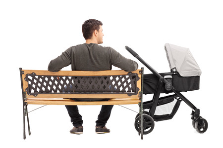 single parents: Rear view studio shot of a young father sitting on bench with baby stroller beside him isolated on white background