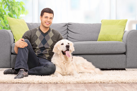 Young man sitting on the floor with his dog at home Stock Photo