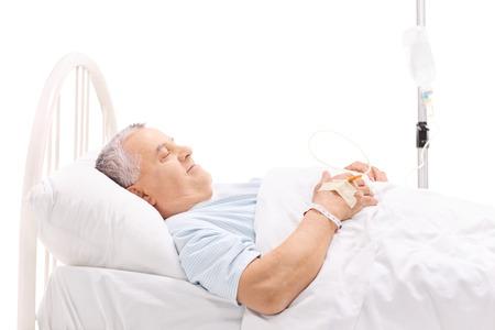 Vrolijke volwassen patiënt liggend in een ziekenhuisbed met een iv infuus gehecht aan zijn hand op een witte achtergrond