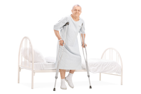 recovery bed: Full length portrait of a mature patient with crutches getting out of bed isolated on white background Stock Photo