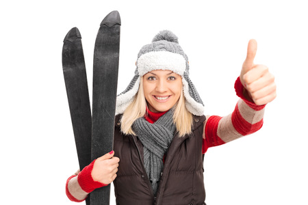 posing  agree: Woman in winter clothes holding skis and giving thumb up isolated on white background