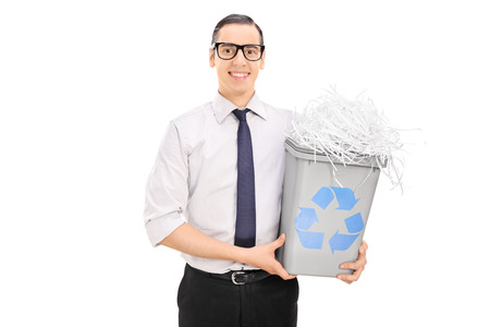 papelera de reciclaje: Hombre joven que sostiene una papelera de reciclaje llena de papel triturado aislado en el fondo blanco