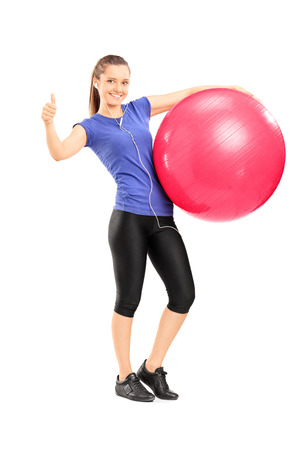 In voller Länge Portrait einer jungen fröhliche Frau mit einem Gymnastikball und geben einen Daumen nach oben isoliert auf weißem Hintergrund