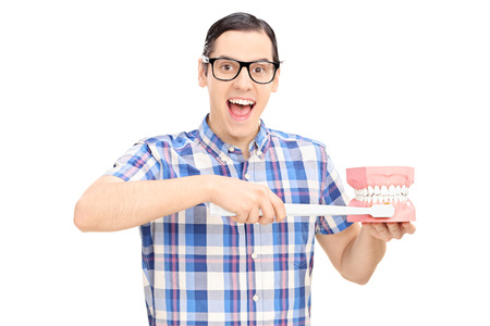 Excited young guy with glasses holding a denture and a toothbrush isolated on white background, studio shot photo