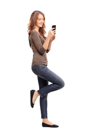 Full length portrait of a young woman typing a text message on her cell phone and leaning against a wall isolated on white background, studio shot Stock Photo
