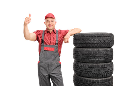 posing  agree: Young repairman in a jumpsuit giving a thumb up and leaning on a stack of tires isolated on white background Stock Photo