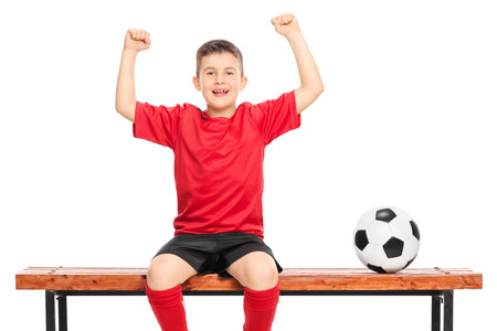 junior soccer: Joyful junior soccer player in red shirt gesturing happiness seated on wooden bench isolated on white background