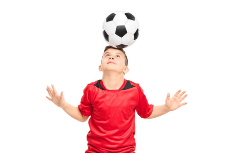 junior soccer: Junior soccer player wearing red shirt joggling with a soccerball isolated on white background