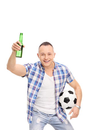 fanatic studio: Vertical studio shot of a young man holding a football and a beer bottle and cheering isolated on white background