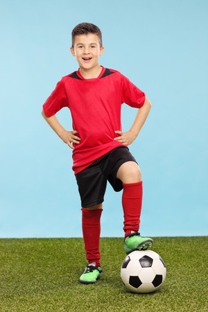 junior soccer: Full length portrait of a junior in a soccer uniform standing over a soccer ball on a grass field with a blue background