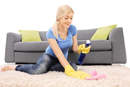 mujer limpiando: Studio foto de una mujer rubia limpiar una alfombra con un spray de limpieza y el uso de guantes de protección amarillas delante de un sofá gris aislado en el fondo blanco