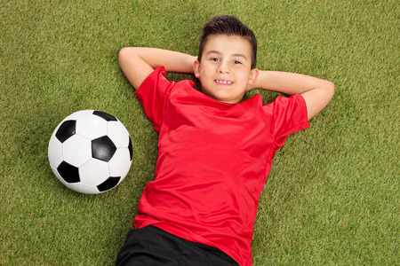 football jersey: Carefree little boy in a red football jersey lying on grass with a ball next to him