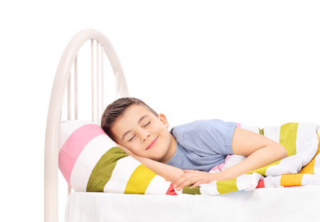 Cheerful little boy sleeping in a comfortable bed and dreaming sweet dreams covered with a blanket isolated on white background photo