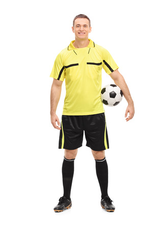 ref: Full length portrait of a male football referee in a yellow jersey holding a ball isolated on white background Stock Photo