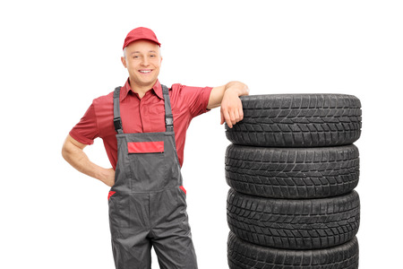 jumpsuit: Male mechanic in a red shirt and gray jumpsuit leaning on a stack of tires isolated on white background Stock Photo