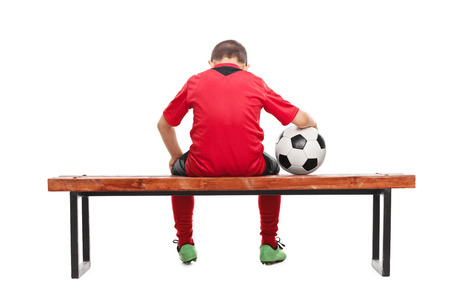 substitution: Rear view studio shot of a sad little boy in red soccer jersey seated on a bench and holding a ball isolated on white background