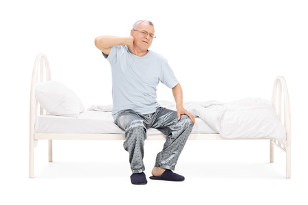 senior man on a neck pain: Senior in pajamas feeling pain in the neck seated on a bed isolated on white background