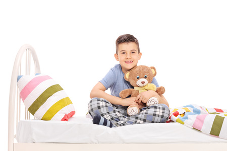 Studio shot of a happy little boy in pajamas, sitting in bed and hugging a teddy bear isolated on white background photo