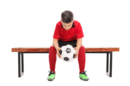 boy ball: Worried little boy in red football shirt sitting on a bench and holding a ball isolated on white background