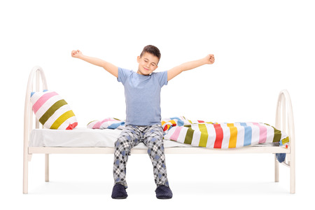 bed: Cute little boy in pajamas stretching himself seated on a bed isolated on white background