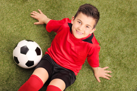 high angle shot: High angle shot of a junior soccer player in red jersey, sitting on a green field and looking at the camera, with a soccer ball beside him
