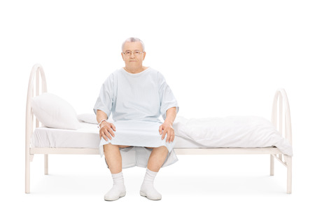 sit studio: Mature patient in a hospital gown sitting on a bed and looking at the camera isolated on white background