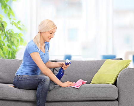 Young blond housewife cleaning a couch with a rag and a cleaning spray at home
